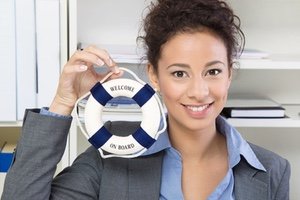 Woman holding small life preserver that says welcome on board